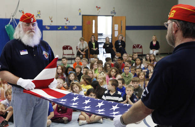 Terry Farmer and Harmon Thompson, members of Veteran's School Flag Program, demonstrate the proper way to fold an American flag to the students at Prairie Vale Elementary School, Thursday, March 15, 2012.  Photo By David McDaniel/The Oklahomen