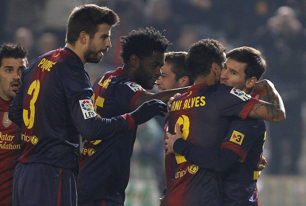 Barcelona's Lionel Messi, right, celebrates with teammates Daniel Alves, second right, Alexandre Song, second left, and Gerard Pique, left, after scoring against Cordoba during the 1st leg of a last-16 Copa del Rey soccer match  at Arcangel stadium in, Cordoba, Spain on Wednesday, Dec. 12, 2012. (AP Photo/Angel Fernandez)