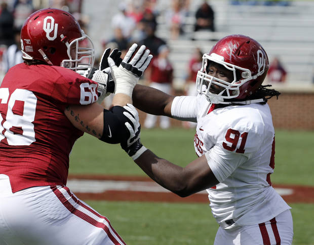 Charles Tapper (91) goes around Bronson Irwin (68) on defense during the annual Spring Football Game at Gaylord Family-Oklahoma Memorial Stadium in Norman, Okla., on Saturday, April 13, 2013. Photo by Steve Sisney, The Oklahoman