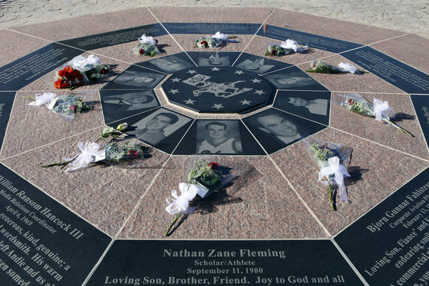 In this Jan. 27, 2011 file photo, flowers adorn the memorial for the victims of a plane crash, where 10 men affiliated with the the Oklahoma State University men's basketball team died, on the 10th anniversary of the crash at a memorial near the crash site near Byers, Colo. Oklahoma State University women's basketball coach Kurt Budke and assistant coach Miranda Serna were killed when the single-engine plane they were riding in during a recruiting trip crashed near a wildlife management area in central Arkansas. The university said the pair died in the crash Thursday night, Nov. 17, 2011. (AP Photo/ Ed Andrieski, File) ORG XMIT: NY156