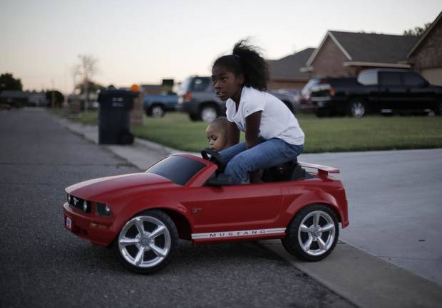 Brianna Young, 9, and Josiah Owens, 1, take a ride around the street in a battery powered car during a National Night Out event at the JFK Neighborhood in Oklahoma City, Tuesday, Sept. 11, 2012.  Photo by Garett Fisbeck, The Oklahoman