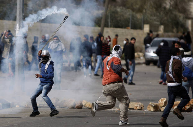 A masked Palestinian throws back a gas canister during a protest to support Palestinian prisoners, outside Ofer, an Israeli military prison near the West Bank city of Ramallah, Friday, Feb. 22, 2013. Israel holds a few thousand Palestinians on charges ranging from throwing rocks to deadly attacks. (AP Photo/Majdi Mohammed)