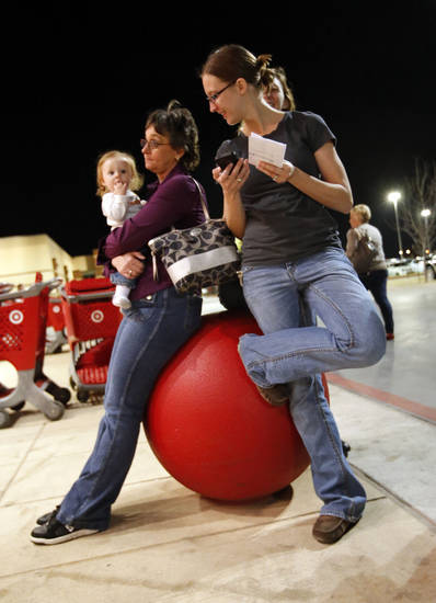 Lori Marshall holds granddaughter Karli Allen as her daughter Linzi checks her list as patrons line up at Target at 9 p.m. for Black Friday Sales on Thursday, Nov. 22, 2012, in Moore, Okla.  Photo by Steve Sisney, The Oklahoman