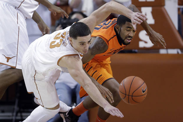 Texas' Ioannis Papapetrou (33) and Oklahoma State's Michael Cobbins, right, scramble for a loose ball during the first half of an NCAA college basketball game, Saturday, Feb. 9, 2013, in Austin, Texas. (AP Photo/Eric Gay) ORG XMIT: TXEG102
