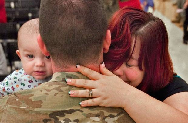 Spc. Galen Scott is greeted by his six-month-old son Benjamin and his wife Jennifer at a ceremony where he and other members of the Oklahoma National Guard were welcomed by family and friends upon their return from Afghanistan on Thursday, Jan. 12, 2012, in Norman, Okla.  Photo by Steve Sisney, The Oklahoman