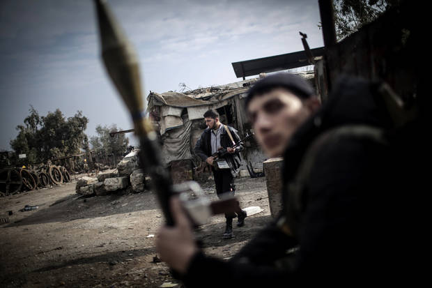 Free Syrian Army fighters hold their weapons during heavy clashes with government forces in Aleppo, Syria, Sunday, Jan. 20, 2013. The revolt against President Bashar Assad began in March 2011with peaceful protests but morphed into a civil war that has killed more than 60,000 people, according to a recent United Nations recent estimate. (AP Photo/Andoni Lubaki)