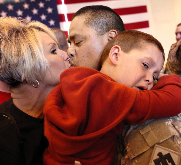Sgt. Evan Wallace with the 45th Infantry Brigade kisses his wife Gaylene, while his 4-year-old grandson Landon hugs him, upon his return in April from deployment to Kuwait and Afghanistan. OKLAHOMAN ARCHIVES <strong>Jim Beckel</strong>