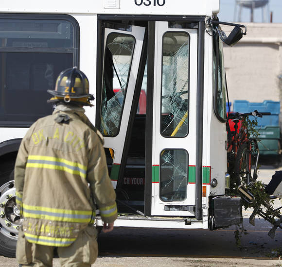 An Oklahoma City firefighter examines a Metro Transit bus after it hit a sport utility vehicle at Linwood Avenue and N Indiana Avenue in Oklahoma City, Thursday, February  16,  2012. Twelve people were taken by ambulance to area hospitals. Photo By Steve Gooch, The Oklahoman