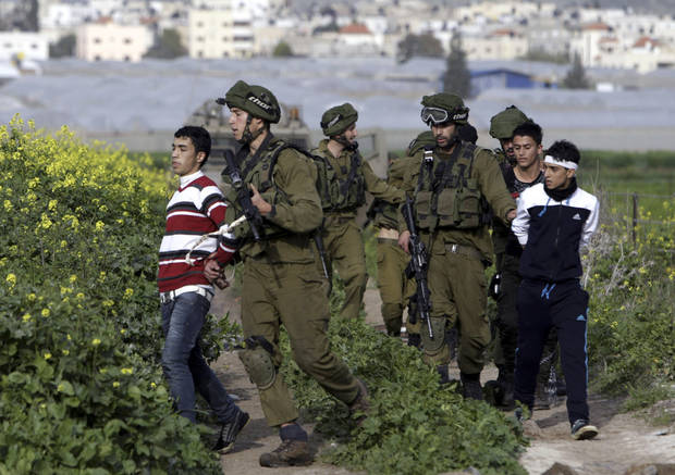 Israeli soldiers arrest Palestinian youth during a protest north of the West Bank city of Jenin in support to the Palestinian prisoners Friday, Feb. 22, 2013.  Israel holds a few thousand Palestinians on charges ranging from rock throwing to deadly attacks.  (AP Photo/Mohammed Ballas)