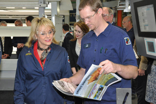 A Quad/Graphics worker shows Gov. Mary Fallin a finished product.PHOTO PROVIDED