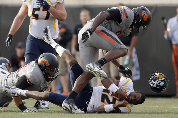 Oklahoma State's Christian Littlehead (72) and Oklahoma State's Ryan Robinson (96) sack West Virginia's Geno Smith (12) during a college football game between Oklahoma State University (OSU) and the West Virginia University at Boone Pickens Stadium in Stillwater, Okla., Saturday, Nov. 10, 2012. Photo by Sarah Phipps, The Oklahoman