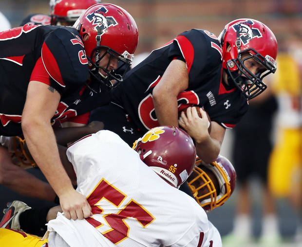 Mustang's Cutter Smith (37) tries to push past Putnam City North's Wendell Mickel (55) for extra yards in front of teammate Tristan Hill (73) during a high school football game between Mustang and Putnam City North in Mustang, Okla., Friday, Sept. 7, 2012. Photo by Nate Billings, The Oklahoman