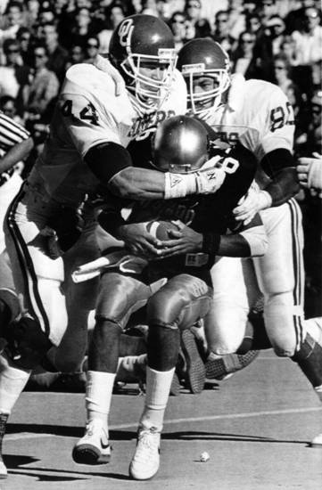 Colorado University quarterback Mark Hatcher has no place to hide as former OU linebackers Brian Bosworth (No. 44) and Troy Johnson close in on Hatcher during a 1986 game. PHOTO BY GEORGE WILSON, The Oklahoman Archives