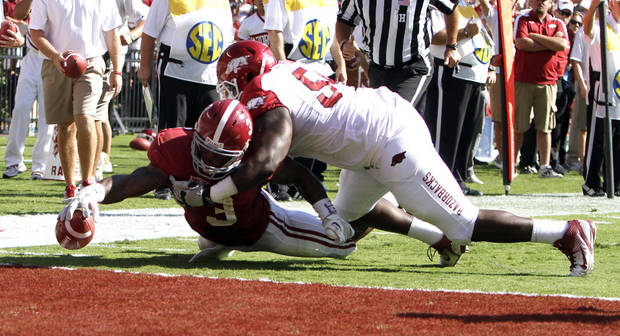 Alabama running back Trent Richardson (3) stretches for the goal line, but comes up short on the stop by Arkansas defensive tackle Byran Jones (54) during the first half of an NCAA college football game on Saturday, Sept. 24, 2011 in Tuscaloosa, Ala. (AP Photo/Butch Dill)