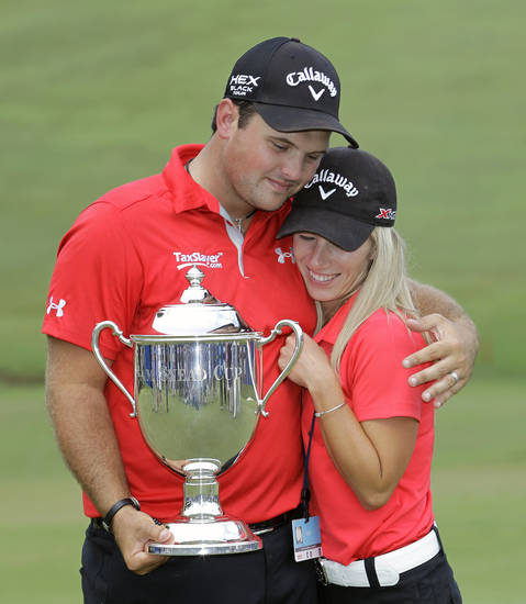 Patrick Reed hugs his wife and caddy, Justine as he holds the Sam Snead trophy after winning the Wyndham Championship golf tournament in a second hole playoff at the Sedgefield Country Club in Greensboro, N.C., Sunday, Aug. 18, 2013. (AP Photo/Bob Leverone)