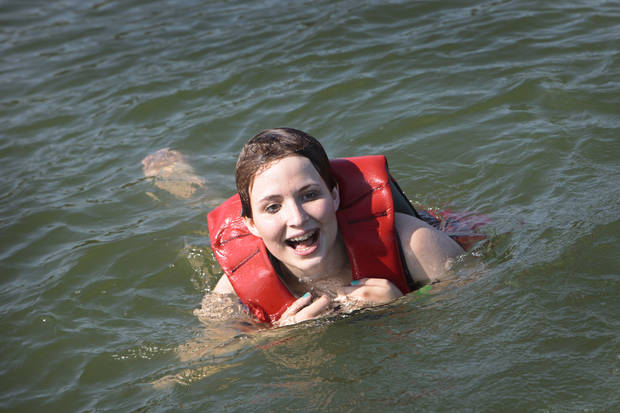 Michela Thompson, 15, swims after fishing at Camp Cavett at Lake Texoma.  <strong>David McDaniel - The Oklahoman</strong>