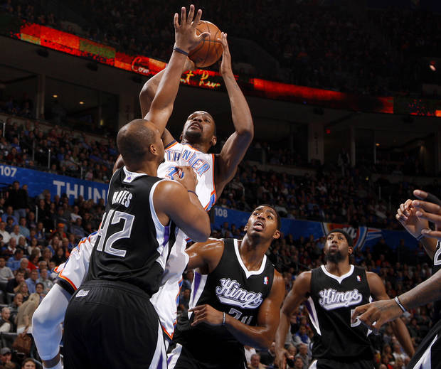 Oklahoma City's Kevin Durant (35) shoots the ball from between Sacramento's Chuck Hayes (42), Jason Thompson (34), and John Salmons (5) during an NBA basketball game between the Oklahoma City Thunder and the Sacramento Kings at Chesapeake Energy Arena in Oklahoma City, Friday, Dec. 14, 2012. Photo by Bryan Terry, The Oklahoman