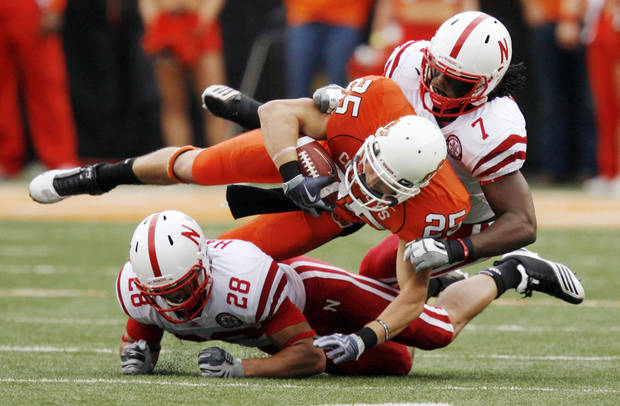 OSU's Josh Cooper (25) is sandwiched between Eric Hagg (28) and DeJon Gomes (7) of Nebraska after a catch in the second quarter during the college football game between the Oklahoma State Cowboys (OSU) and the Nebraska Huskers (NU) at Boone Pickens Stadium in Stillwater, Okla., Saturday, Oct. 23, 2010. Photo by Nate Billings, The Oklahoman