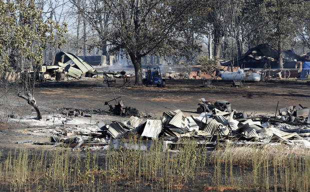 The remains of Harold and Vicky Grigg's home and outbuildings at 6830 132nd Street  still smolder from Friday's wildfire on Saturday, Aug. 4, 2012, in Slaughterville, Okla.  Photo by Steve Sisney, The Oklahoman