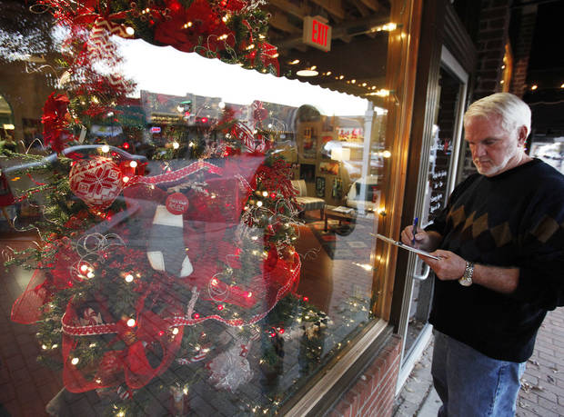 Bob Palmer, from the University of Central Oklahoma, judges the downtown business windows that are decorated for Christmas. PHOTOs BY DAVID MCDANIEL, THE OKLAHOMAN