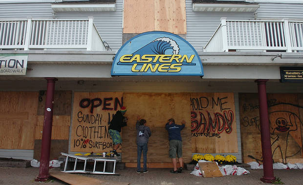 Business owners along Ocean Avenue in Belmar, N.J., board up windows and sandbag their properties on Sunday, Oct. 28, 2012, in preparation for Hurricane Sandy. (AP Photo/The Record of Bergen County, Kate Collins) ONLINE OUT; MAGS OUT; TV OUT; INTERNET OUT;  NO ARCHIVING; MANDATORY CREDIT ORG XMIT: NJHAC201