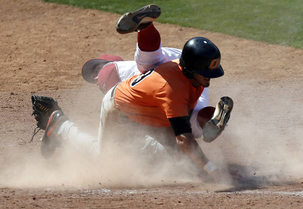 Oklahoma's Jacob Evans collides with  Oklahoma State's Aaron Cornell at home plate during the Bedlam baseball game between the University of Oklahoma and Oklahoma State University at the Chickasaw Bricktown Ballpark in Oklahoma CIty, Sunday, May 12, 2013. Cornell was called out. Photo by Sarah Phipps, The Oklahoman