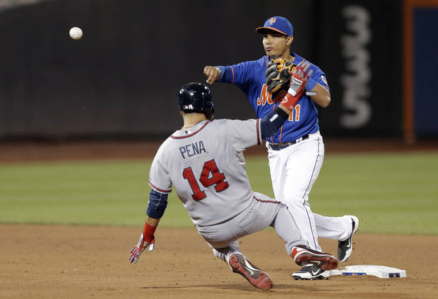 New York Mets shortstop Ruben Tejada (11) throws to first putting out Atlanta Braves' Ramiro Pena (14) after Braves' Andrelton Simmonds hit into an eighth-inning double play during their baseball game at Citi Field in New York, Sunday, May 26, 2013. (AP Photo/Kathy Willens)