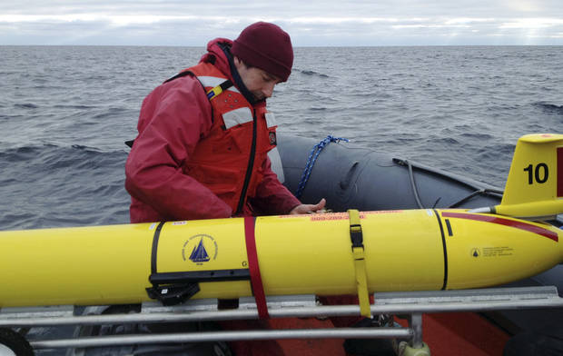 In this Dec. 4, 2012 photo, Woods Hole Oceanographic Institution chief scientist Mark Baumgartner, aboard a ship in the Gulft of Maine, secures an underwater robot, or glider, used to collect acoustic data to help scientists locate endangered whales in the north Atlantic Ocean. (AP Photo/Woods Hole Oceanographic Institution, Nadine Lysiak)