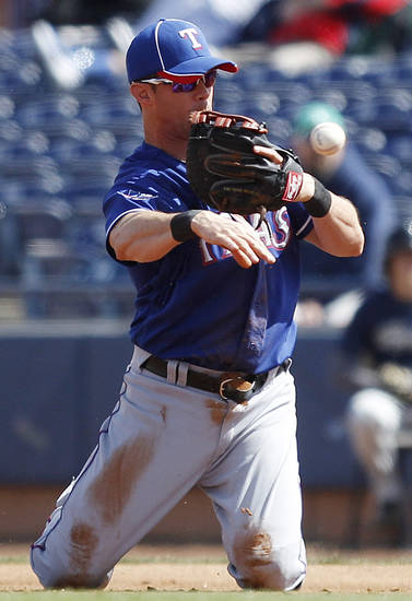 FILE - In this March 7, 2012, file photo, Texas Rangers first baseman Michael Young throws out San Diego Padres' Mark Kotsay after making a diving stop that saved a run from scoring during the second inning of a spring training baseball game in Peoria, Ariz. A person familiar with the trade says the Philadelphia Phillies have acquired the seven-time All-Star from the Texas for two relief pitchers. Young agreed to waive his no-trade clause on Saturday, Dec. 8, 2012, the person said, speaking on condition of anonymity because the deal hasn't been announced.  (AP Photo/Lenny Ignelzi , File)
