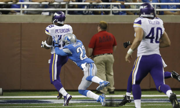 Detroit Lions cornerback Chris Houston (23) reaches Minnesota Vikings running back Adrian Peterson (28) as he scores a touchdown on the Vikings' first possession of NFL football game in Detroit, Sunday, Sept. 8, 2013. (AP Photo/Carlos Osorio)