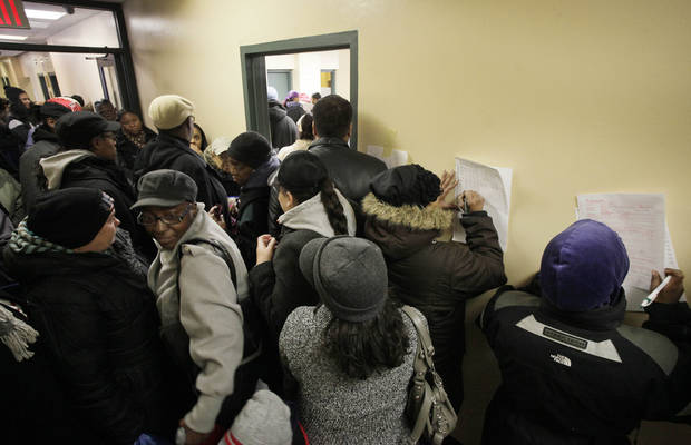 Two people fill out ballots against a wall as other voters crowd an apartment building hallway as they wait to enter a temporary polling station, center, Tuesday, Nov. 6, 2012 in the Coney Island section of New York.  Voting in the U.S. presidential election was the latest challenge for the hundreds of thousands of people in the New York-New Jersey area still affected by Superstorm Sandy, as they struggled to get to non-damaged polling places to cast their ballots in one of the tightest elections in recent history. (AP Photo/Mark Lennihan) ORG XMIT: NYML106