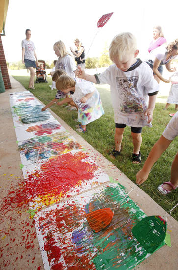 Left: Tyler Frankenfield, 3, slaps some paint as children paint with flyswatters Monday at the Edmond Multipurpose Activity Center.