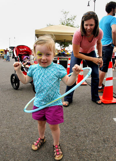 Courtney Grteen gives daughter Cora, 2, a spin with hula hoops in the children's area during the Norman Music Festival on Saturday, April 28, 2012, in Norman, Okla.  Photo by Steve Sisney, The Oklahoman