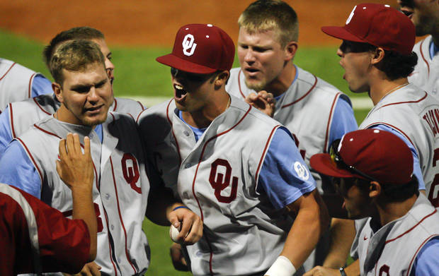 Oklahoma's Max White, center, celebrates with teammates Kolbey Carpenter, left, and Colt Beckerstaff, right, during an NCAA college baseball tournament regional game at English Field in Blacksburg, Va., Sunday, June 2, 2013.  (AP Photo/Michael Shroyer) ORG XMIT: VAMS160