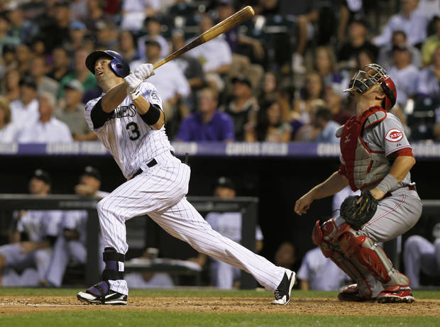 Colorado Rockies' Michael Cuddyer, left, follows the flight of his fly out with Cincinnati Reds catcher Devin Mesoraco in the fourth inning of a baseball game in Denver on Saturday, Aug. 31, 2013. (AP Photo/David Zalubowski)