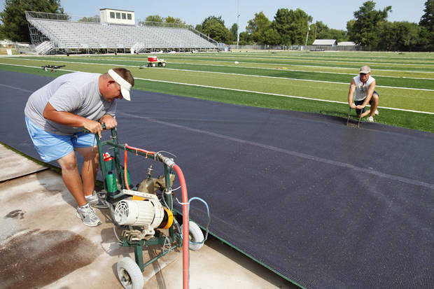 Kent French uses a pneumatic sewing machine in August to join two pieces of artificial turf on the Alcott Middle School football field, which is one of 51 capital projects in the 2009 bond issue. OKLAHOMAN ARCHIVE PHOTO