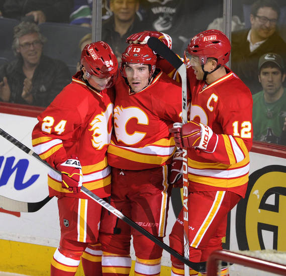 Calgary Flames' Mike Cammalleri, centre, celebrates his goal against the Vancouver Canucks with Jarome Iginla, right, and Jiri Hudler, of the Czech Republic, during first period NHL action in Calgary on Sunday, March 3, 2013. (AP Photo/The Canadian Press, Larry MacDougal)