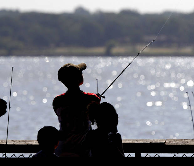 "Kids fish off the pier at Lake Overholser in Oklahoma City earlier this summer. Last year the Oklahoma Department of Wildlife Conservation piloted a ""Fishing in the Schools"" program in 40 public schools in the state. The agency is adding 100 more schools this year. It's similar to the ""Archery in the Schools"" program that the Wildlife Department started in state schools eight years ago. Photo By Paul Hellstern, The Oklahoman"
