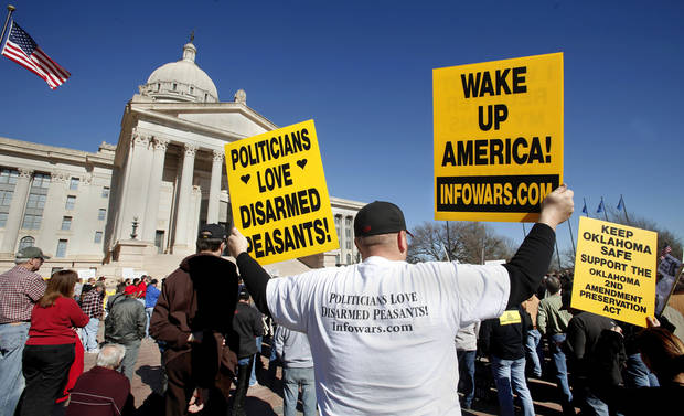 "Lance Gentry of Chouteau, Okla.,  holds two of three signs he brought to the rally.  Organizers said an estimated 1800 people from throughout Oklahoma crowded into the south plaza of the state Capitol Saturday afternoon, Jan. 19, 2013, to voice their support for their second amendment rights and to express  concerns about proposed gun control legislation being considered by the federal government in the wake of the school shooting in Connecticut last month. Many  held aloft hand-made signs or waved American flags as speakers addressed the gun rights rally.  Travis attended with his wife. He said he created the sign he holds. Gentry brought his family with him and said he came because he ""is a law abiding citizen"" and he felt he needed to ""stand up for freedoms.""  Photo by Jim Beckel, The Oklahoman"