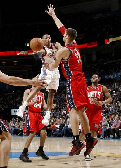 Oklahoma City's Russell Westbrook passes the ball past New Jersey's Brook Lopez during the NBA basketball game between the Oklahoma City Thunder and the New Jersey Nets at the Oklahoma City Arena, Wednesday, Dec. 29, 2010.  Photo by Bryan Terry, The Oklahoman