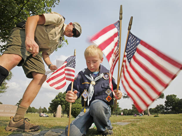 Cub Scout leader Frank Sherman and Bear Logan Weber place flags on veterans graves in Edmond's Memorial Park Cemetery for Memorial Day, Thursday, May 24, 2012. Photo By David McDaniel/The Oklahoman