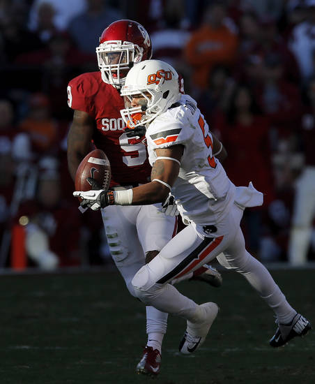 Oklahoma State's Josh Stewart (5) makes a catch against Oklahoma's Gabe Lynn (9) during the Bedlam college football game between the University of Oklahoma Sooners (OU) and the Oklahoma State University Cowboys (OSU) at Gaylord Family-Oklahoma Memorial Stadium in Norman, Okla., Saturday, Nov. 24, 2012. Photo by Nate Billings , The Oklahoman