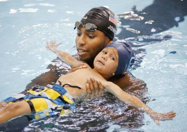 Olympic gold medalist Cullen Jones works with Charlie Zeeck, 3, on Thursday at the Oklahoma City Community College pool. Jones is touring the country as part of the Make a Splash program, an anti-drowning intiative created by the USA Swimming Foundation. <strong>PAUL HELLSTERN - THE OKLAHOMAN</strong>