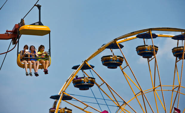 Visitors to the midway take a ride on the big swing during the 2013 Oklahoma State Fair on Monday, Sep. 16, 2013. Photo by Chris Landsberger, The Oklahoman