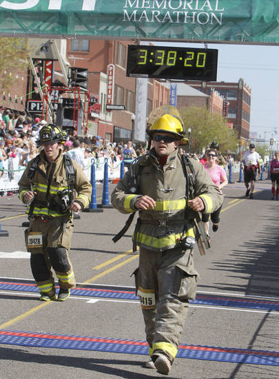 Firefighter Preston Hensley sprints across the line of the half-marathon in full firefighting gear during the Oklahoma City Memorial Marathon in Oklahoma City, Sunday, April 28, 2013,  By Paul Hellstern, The Oklahoman
