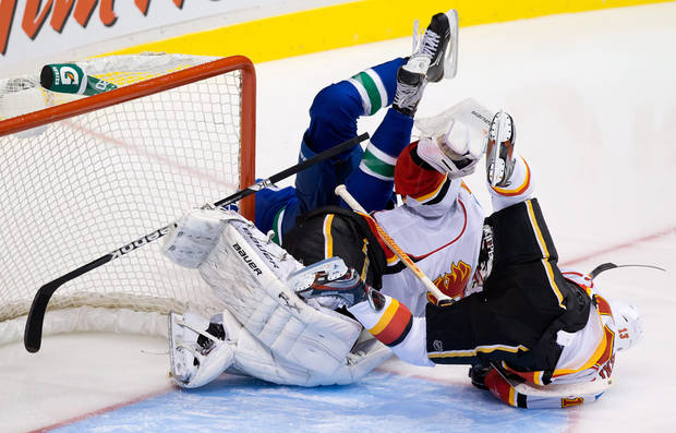 Vancouver Canucks' Zack Kassian, left, crashes into Calgary Flames goalie Miikka Kiprusoff, of Finland, and Mike Cammalleri, right, during the third period of an NHL hockey game in Vancouver, British Columbia. (AP Photo/The Canadian Press, Darryl Dyck)