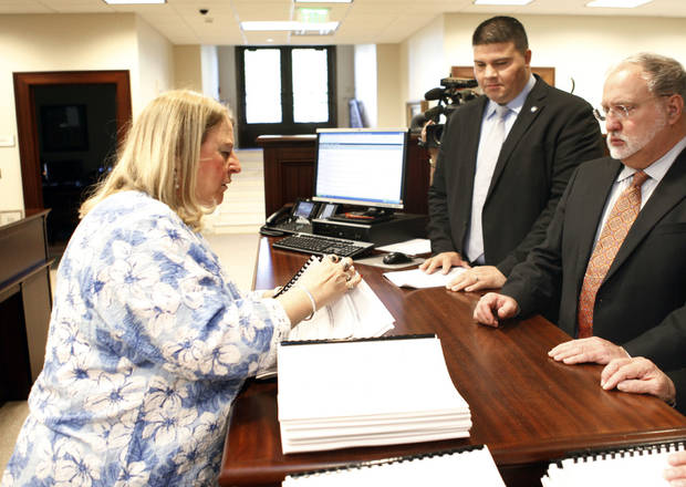 At the Oklahoma Judicial Center, First Deputy Court Clerk Susan Hampton stamps appeal documents filed Monday by Doug Friesen, right, an attorney for convicted murderer Jerome Ersland. Sen. Ralph Shortey, an Ersland supporter, watches the process.  <strong>PAUL HELLSTERN - Oklahoman</strong>