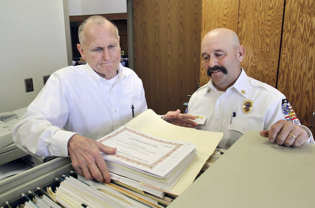 Outgoing Edmond Deputy Fire Chief Arnie Postier (left) and Incoming Deputy Fire Chief Ryan Lenz look over personnel files at the Fire Department's administrative offices in Edmond, OK, Monday, March 5, 2012. Postier is retiring March 9 and Lenz has been promoted to take his place. By Paul Hellstern, The Oklahoman