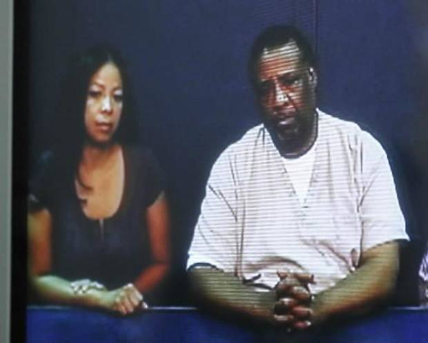 Larry Yarbrough, right, is pictured on a television screen seated next to his daughter, LaDonna Yarbrough, left, during a video conference commutation hearing at the Oklahoma Pardon and Parole Board in Oklahoma City, Wednesday, Aug. 17, 2011.  (AP Photo/Sue Ogrocki)