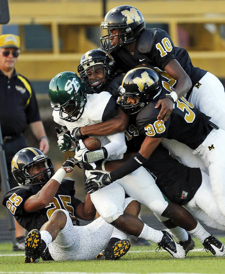 Edmond Santa Fe's Trevan Smith (2) is gang tackled on a kick return during the high school football game between Midwest City and Edmond Santa Fe at Rose Field in Midwest City, Okla., Thursday, Aug. 30, 2012. Photo by Nate Billings, The Oklahoman